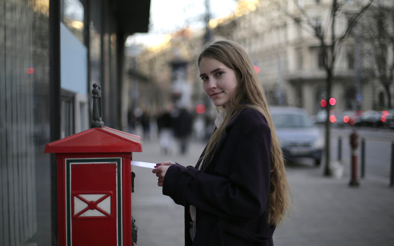 a woman is sending a postcard