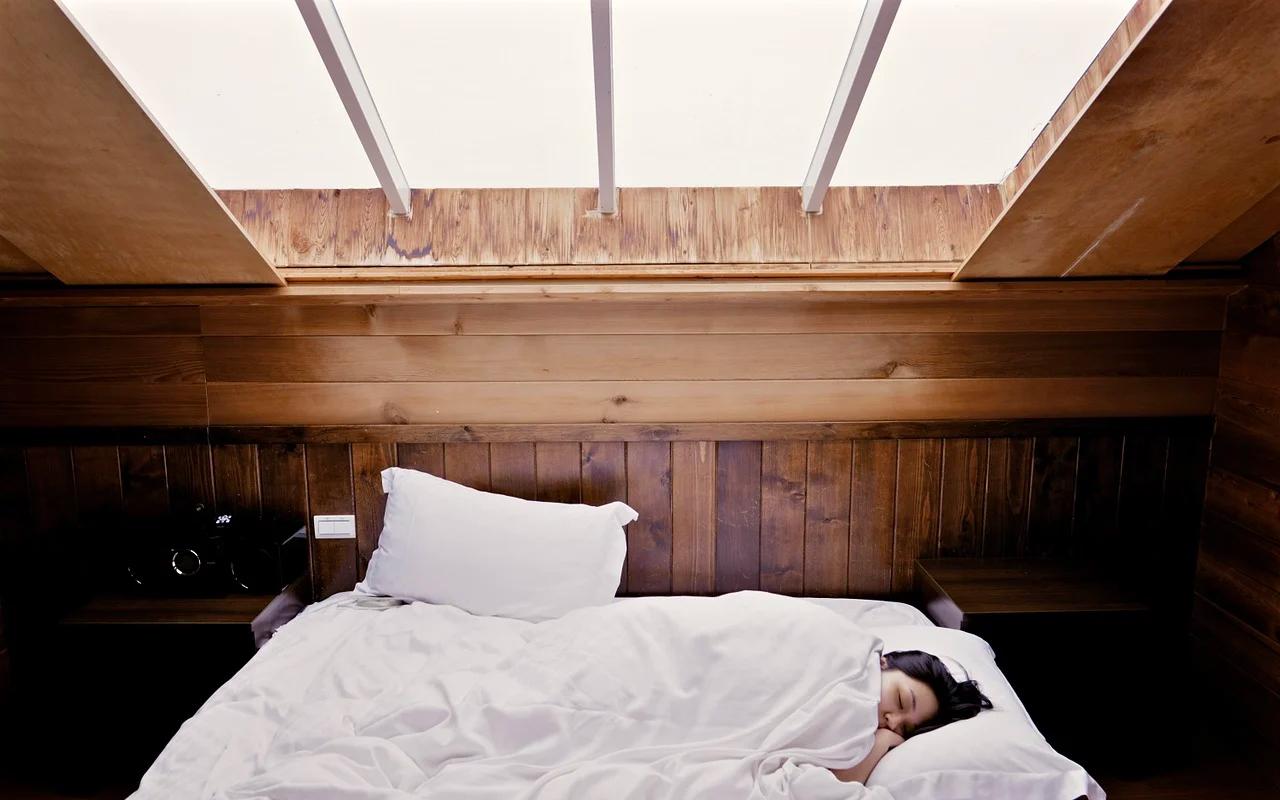 a woman is sleeping under a window