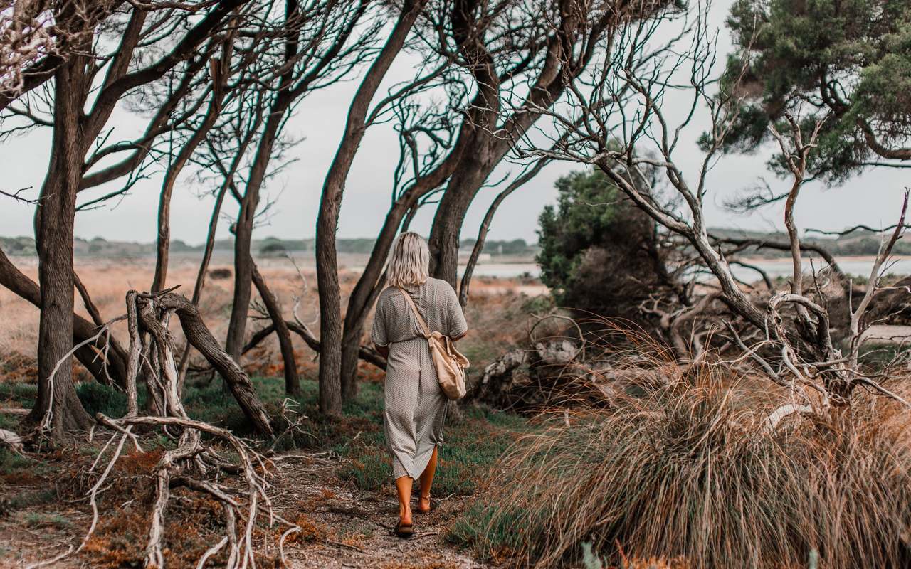 a woman is walking between tree roots