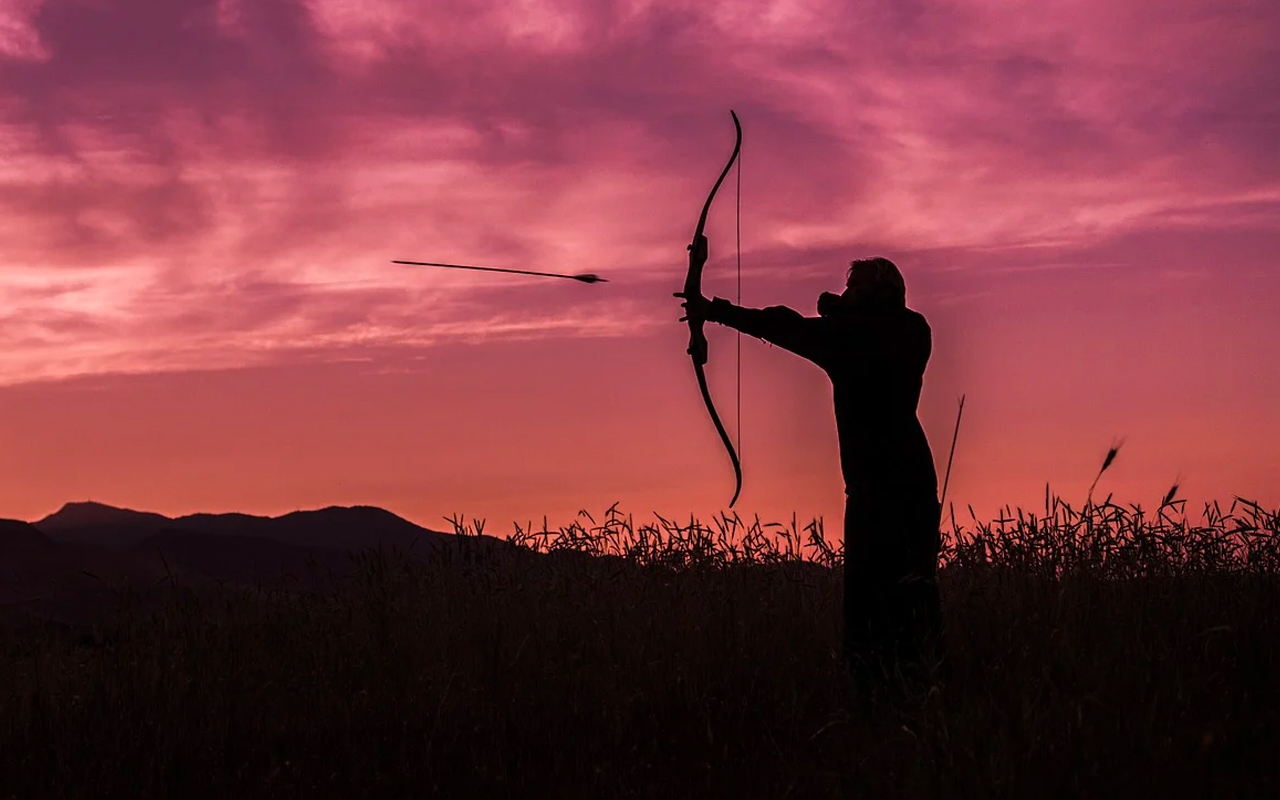 a man is shooting with a bow and arrows