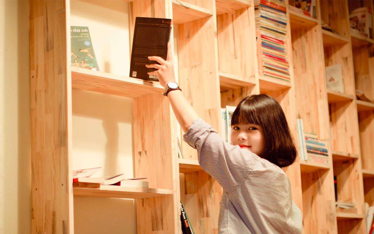 a woman getting a book from a shelf
