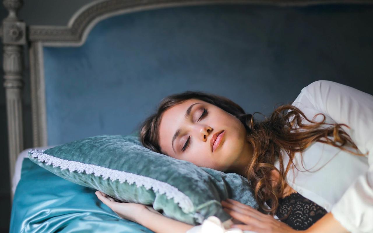 a women is sleeping on a blue pillow