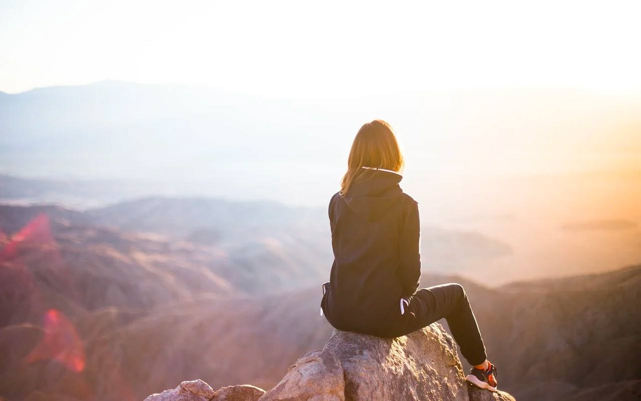 a woman is sitting on a rock with mountain view