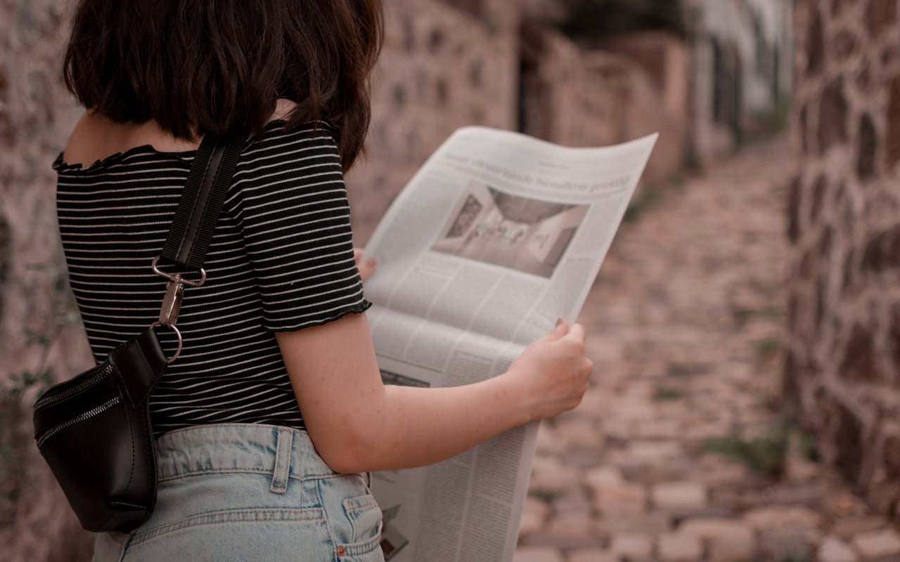 a woman is reading a newspaper