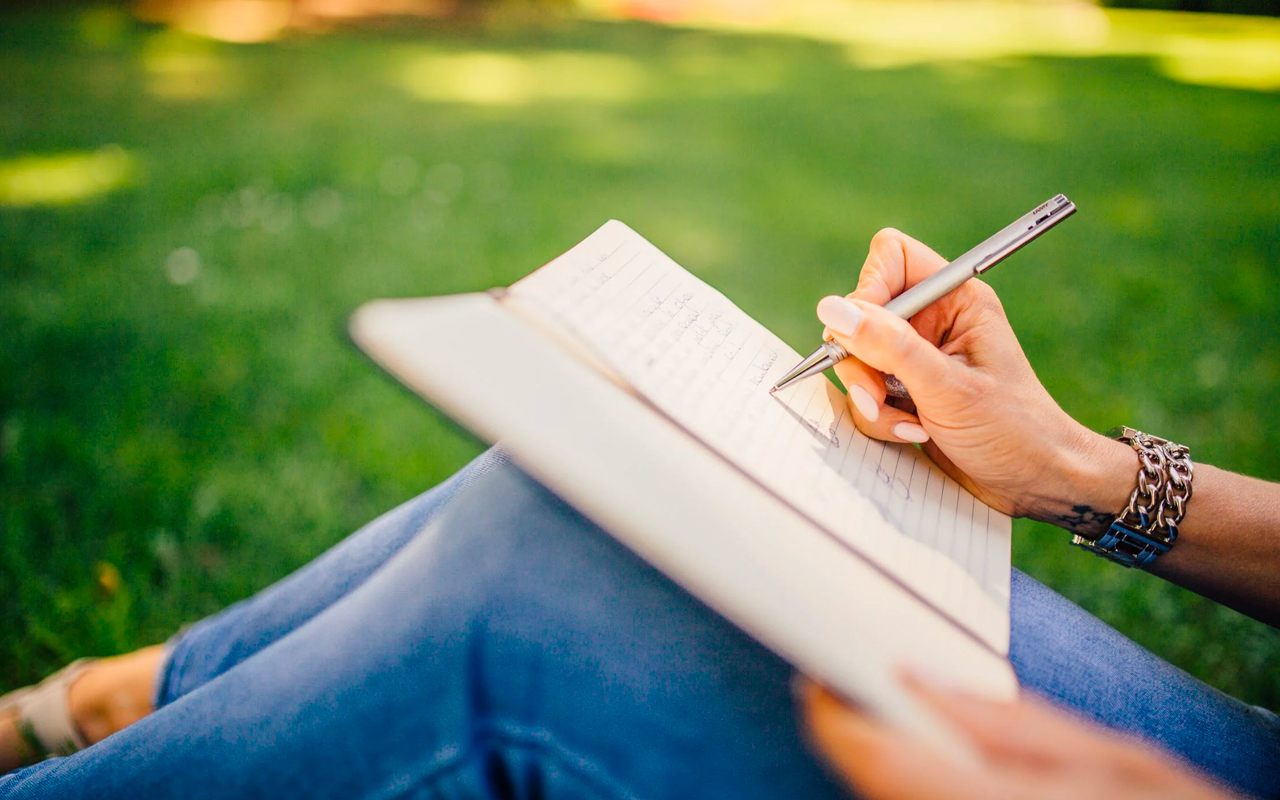 a woman is writing on a journal