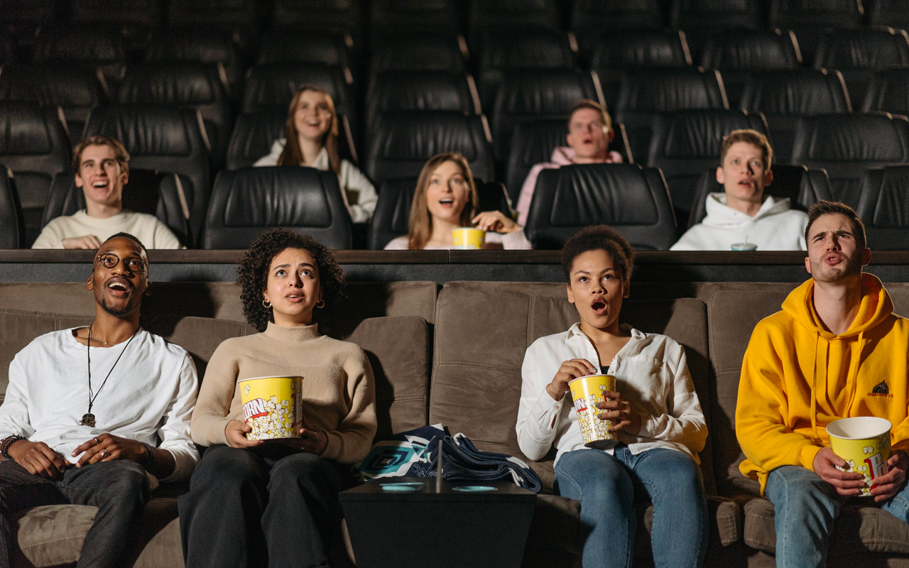 people watching a movie and eating popcorns