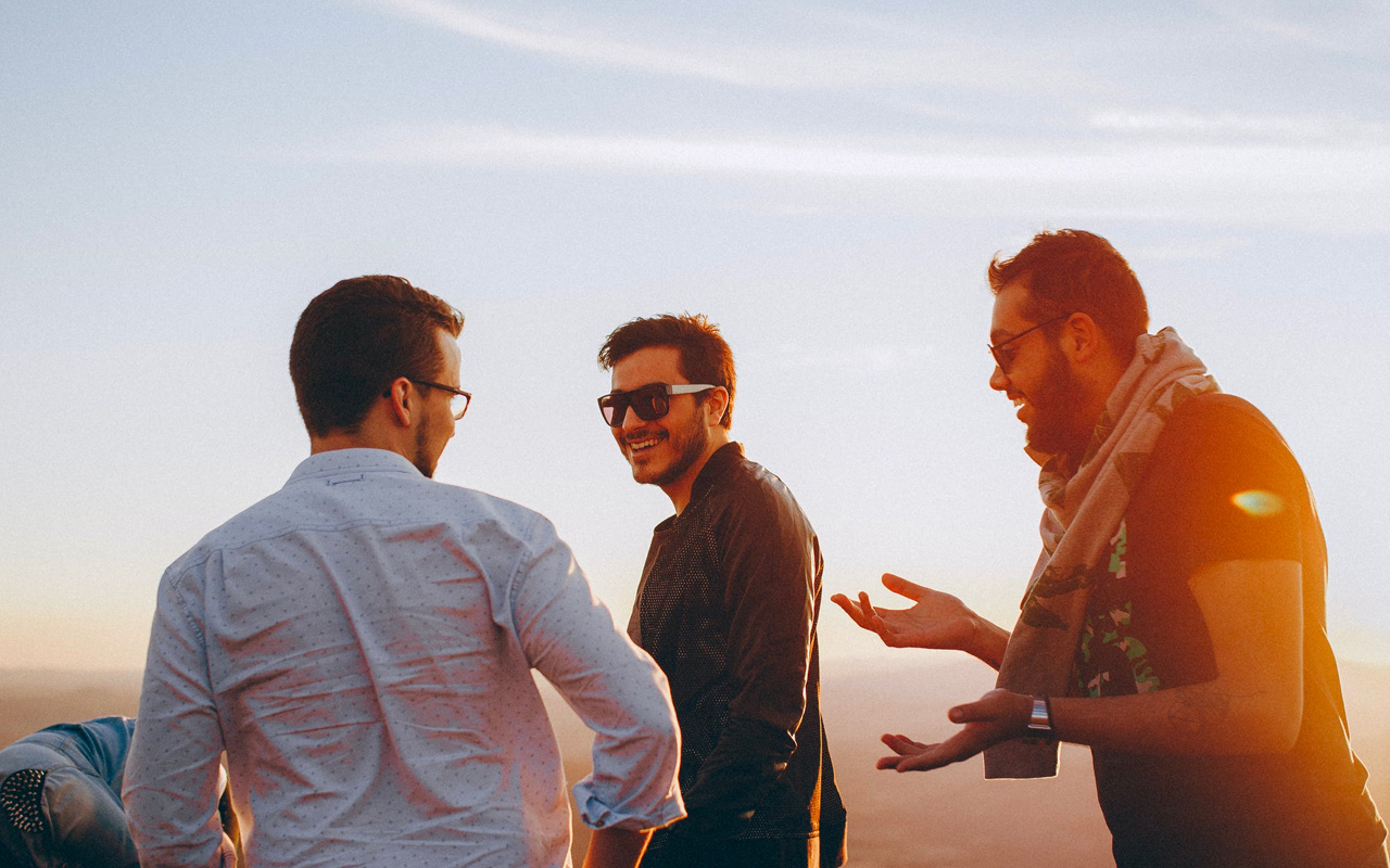 three man are talking with each other