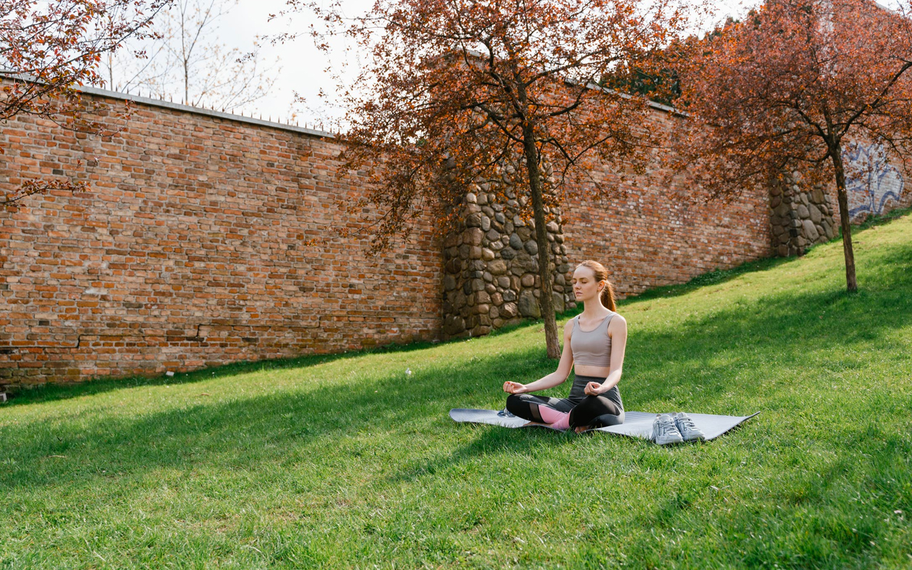 a girl is meditating in red wall park