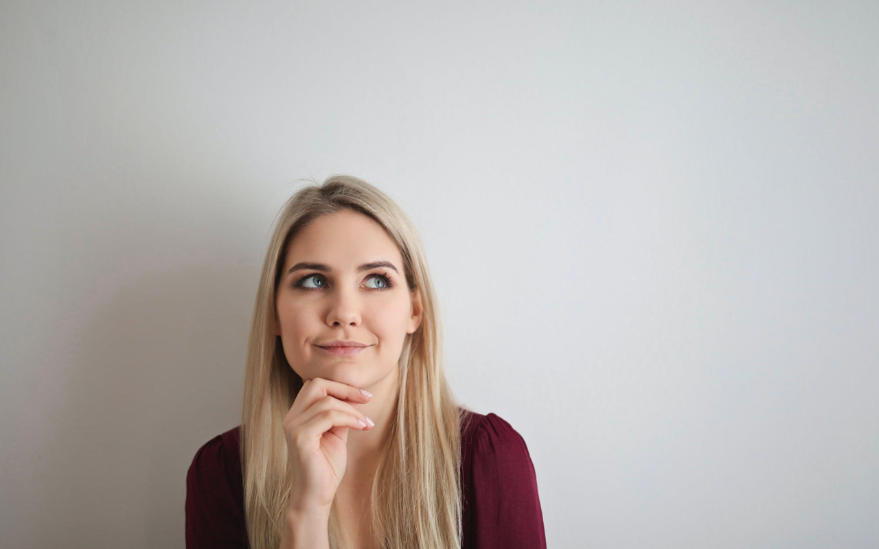 a woman is thinking in front of a white board