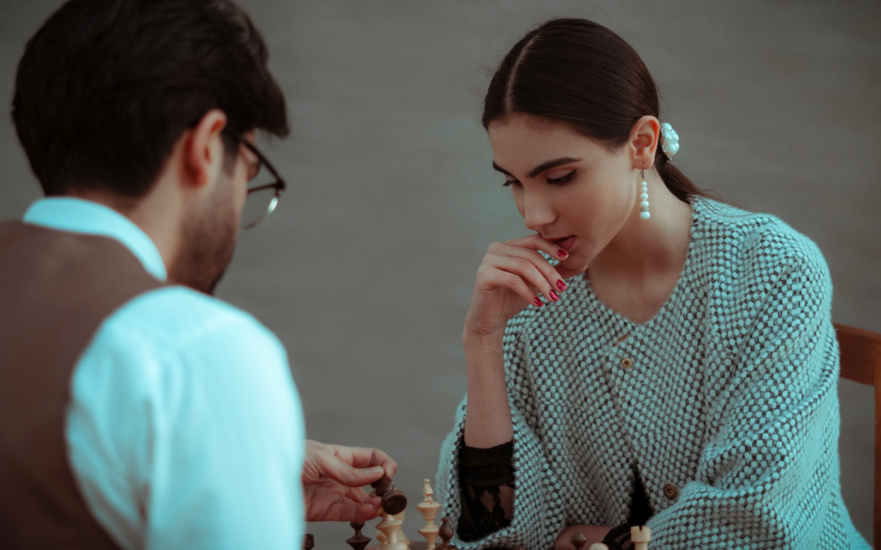 long hair woman and glasses man are playing chess