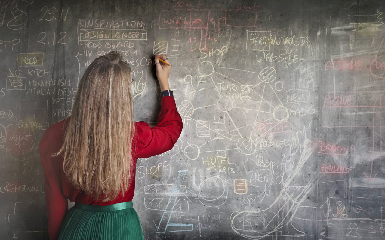 long hair woman drawing on a chalkboard